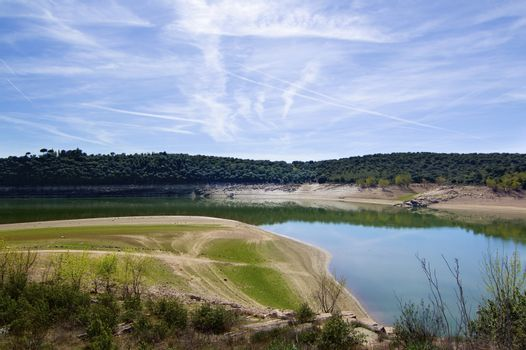 Embalse de Ricobayo with Reflection of Green Trees against Cloudy Sky in Sunny Day Outdoors. Zamora, Castilla and Leon, Spain