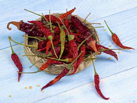 Heap of Dried Chili Peppers Full Body with Stems  and Seeds in Wicker Bowl closeup on Light Blue Wooden background