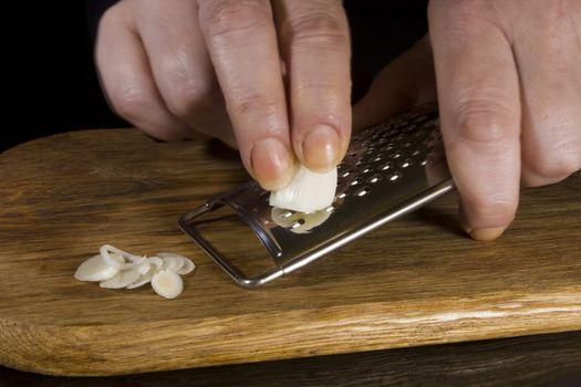 Female hands grind garlic