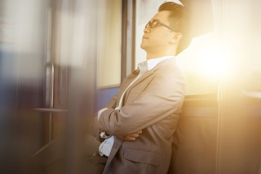 Asian businessman taking a nap inside train while travelling to work.