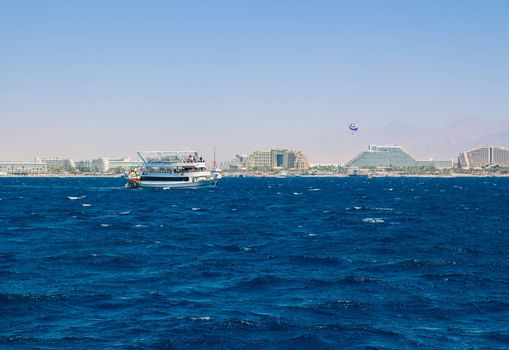 Yacht sailing in the Red Sea. In the background the hotel strip of Eilat.