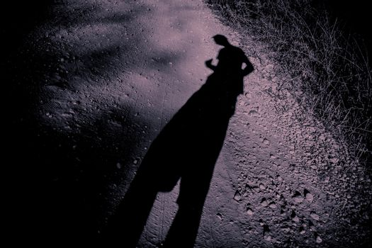 Elongated shadow of a man on gravel