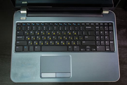 Keyboard with letters in Hebrew and English - Laptop keyboard - Top View -  Dark atmosphere