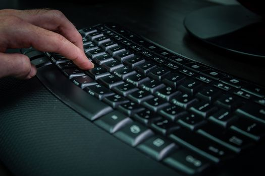Man typing on a keyboard with letters in Hebrew and English - Wireless keyboard - Dark atmosphere