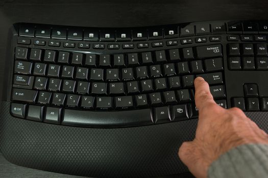 Man typing on a Wireless keyboard with letters in Hebrew and English - Press the Enter key - Top View