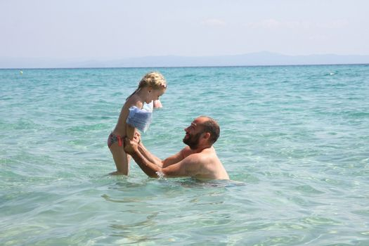 Father and daughter playing in the clear sea water