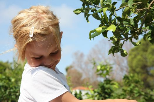 Portrait of cute baby girl posing near leafage