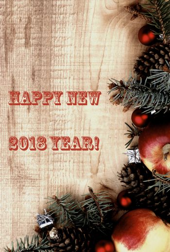 New Year Decoration with Spruce Branch, Red Baubles, Fir Cones, Apples and Inscription 2018 closeup on Wooden background