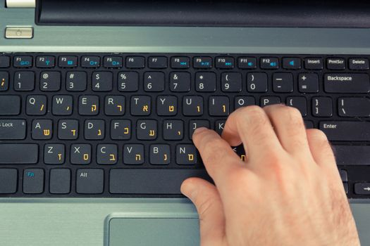 Man typing on a keyboard with letters in Hebrew and English - Laptop keyboard - Top View