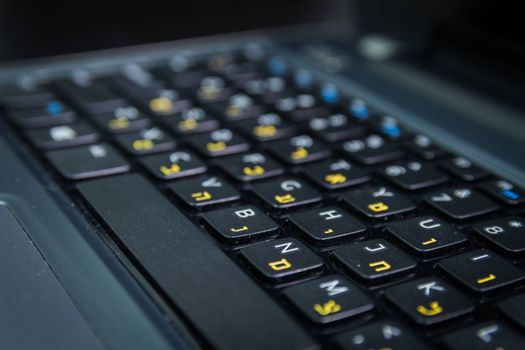 Keyboard with letters in Hebrew and English - Laptop keyboard - Close up - Dark atmosphere