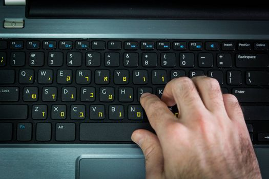 Man typing on a keyboard with letters in Hebrew and English - Laptop keyboard - Top View - Dark atmosphere