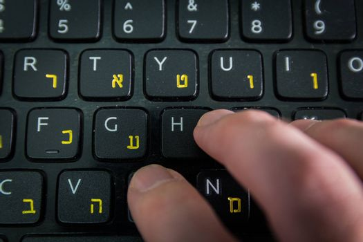 Man typing on a keyboard with letters in Hebrew and English - Laptop keyboard - Top View - Close up_Dark atmosphere