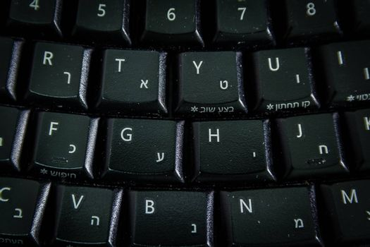 Keyboard with letters in Hebrew and English - Wireless keyboard - Top View - Close up - Dark atmosphere