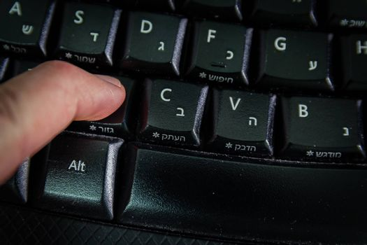 Man typing on a Wireless keyboard with letters in Hebrew and English - Press the Cut button - Top View - Dark atmosphere