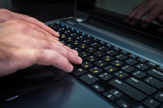 Man typing on a keyboard with letters in Hebrew and English - Laptop keyboard_Dark atmosphere