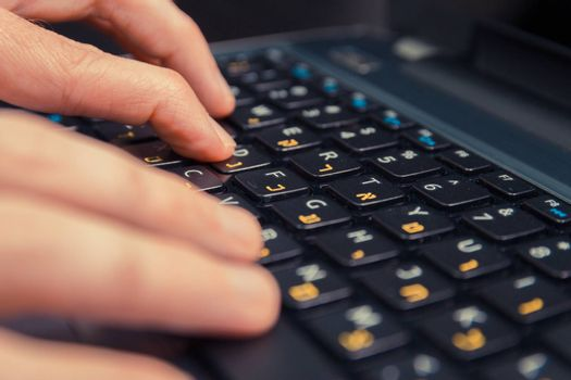 Man typing on a keyboard with letters in Hebrew and English - Laptop keyboard - Close up