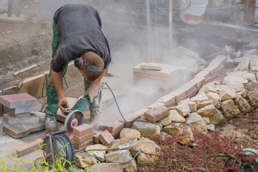 Man cutting stone slabs, concrete slab with an electric grinder