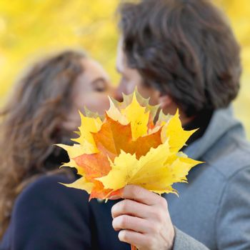 Love, relationship, family and people concept - couple kissing in autumn park
