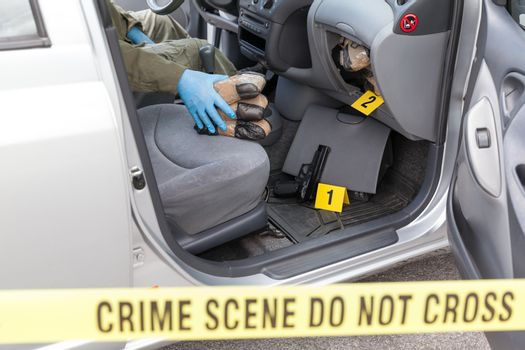 Police officer holding drug packages found in secret compartment of a car