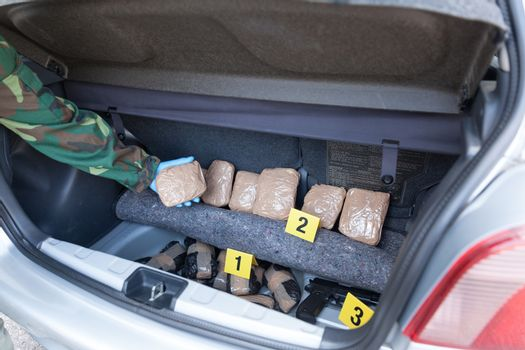 Policeman holding drug package discovered in the trunk of a car