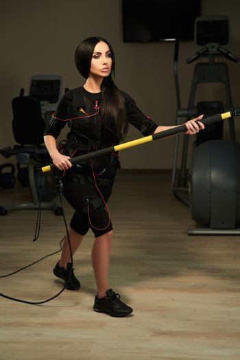 EMS fitness woman with a bar on flexible band