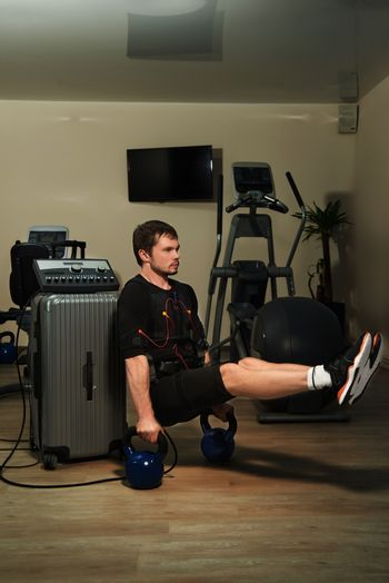 Man in EMS suit doing L-Sit plank on weights