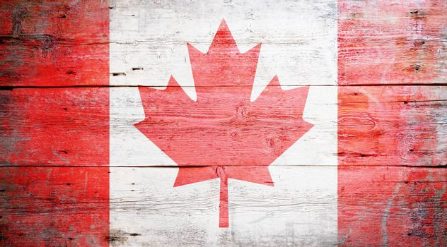 Flag of Canada painted on grungy wood plank background