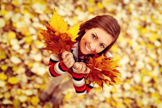 Beautiful young woman enjoying in sunny forest in autumn colors. She is holding golden yellow leaves. Looking at camera. Top view.