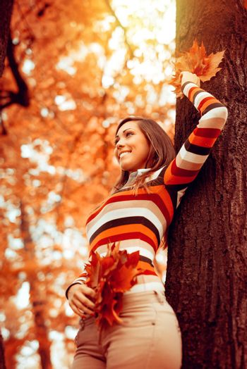 Beautiful young woman enjoying in sunny forest in autumn colors. She is holding golden leaves and standing next to tree.