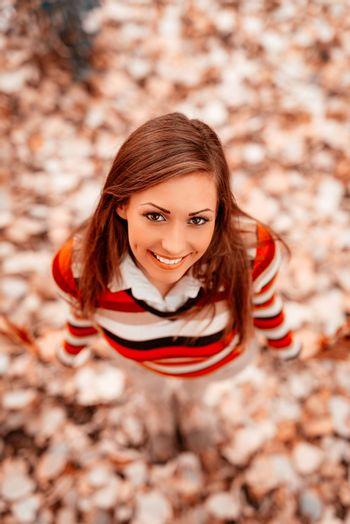 Top view of a beautiful young woman enjoying in forest in autumn colors. Looking at camera.