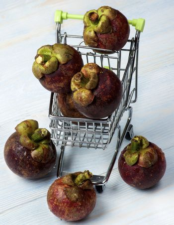 Arrangement of Fresh Mangosteen in Trolley closeup on Blue Wooden background