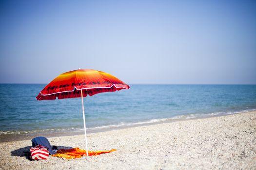 Red umbrella on tropical beach, Italian summer