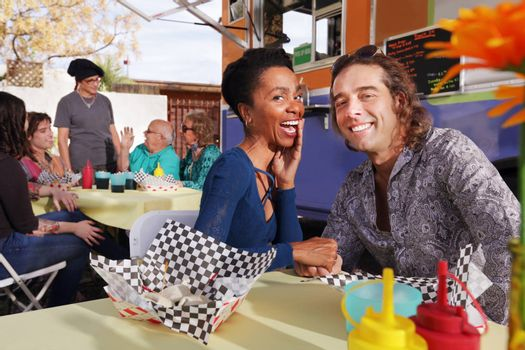 Smiling handsome diverse couple sits at table beside food truck outside