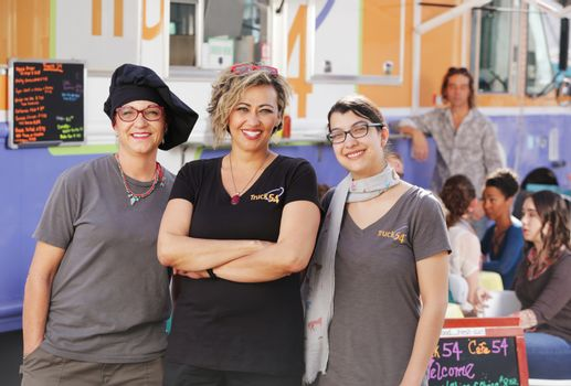 Three smiling food truck entrepreneurs in front of their food truck outdoors