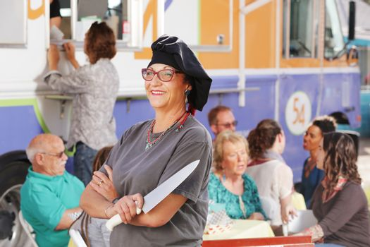 Fast food cook stands beside her truck wearing chef's hat and holding a large knife