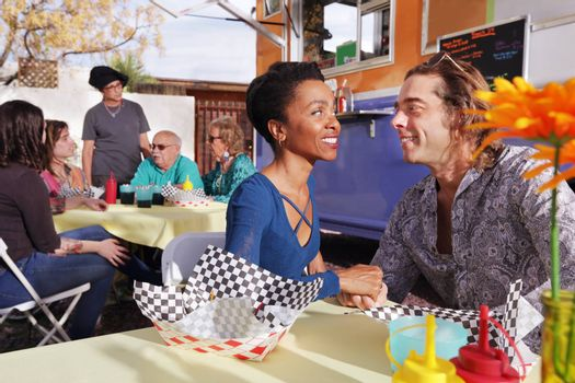Diverse couple smiles at one another while seated beside a food truck