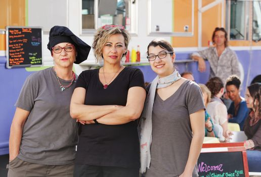 Three food workers posing in front of an outdoor food truck
