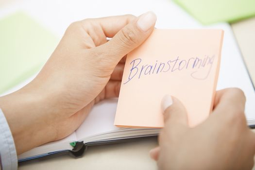 Hands holding sticky note with Brainstorming text