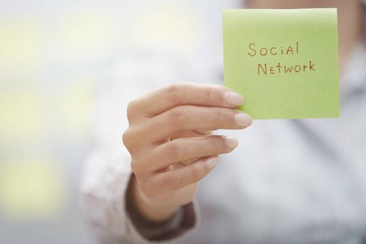 Woman holding sticky note with Social network text