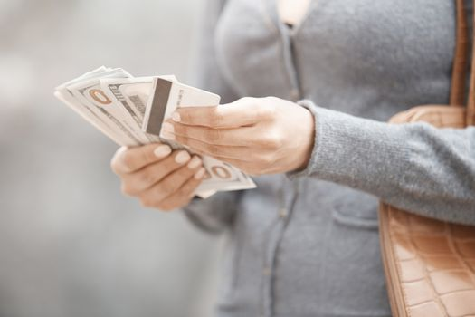 Woman holding cash money and credit card