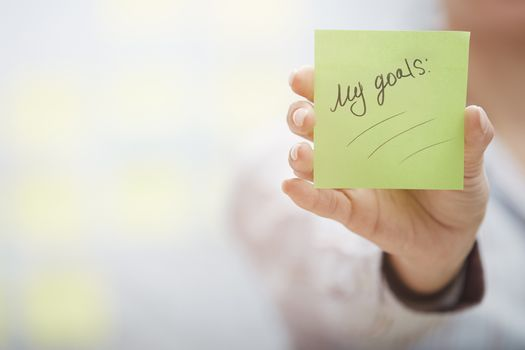 Woman holding sticky note with goals planning