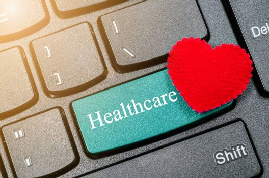 Computer keyboard and red heart with word Healthcare.