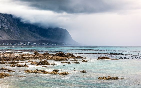 Beautiful landscape of Betty's Bay, mountains in the fog near seashore, beauty of wild nature, Atlantic Ocean, South Africa