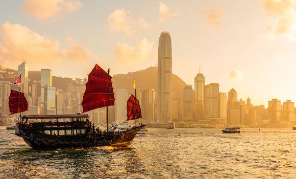 Chinese wooden red sails ship in Hong Kong Victoria harbor at su