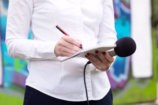 Female reporter taking notes at news conference, writing notes, holding microphone
