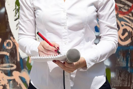 Female reporter at press event, taking notes, holding microphone