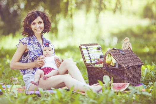 Young beautiful mother sits with her daughter on blanket in park