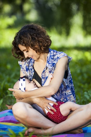Young mother breast feeding a baby in the park