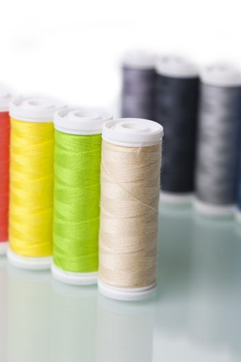 Sewing equipment and  threads on white background.