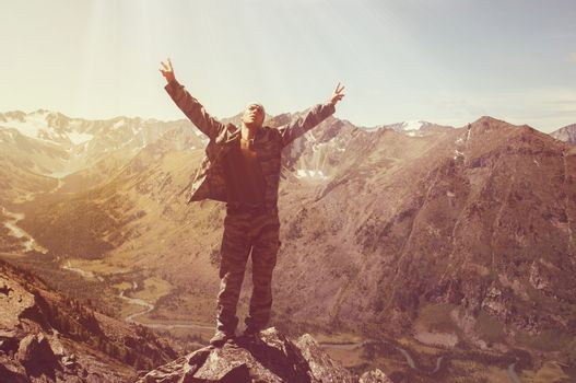 Hiker standing on top of a mountain with raised hands and enjoying sunrise. Tourists with raised arms in the background of a beautiful mountain landscape with a lake and a river